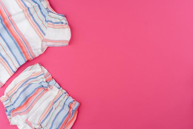 분홍색 배경 평면도에 아기 옷