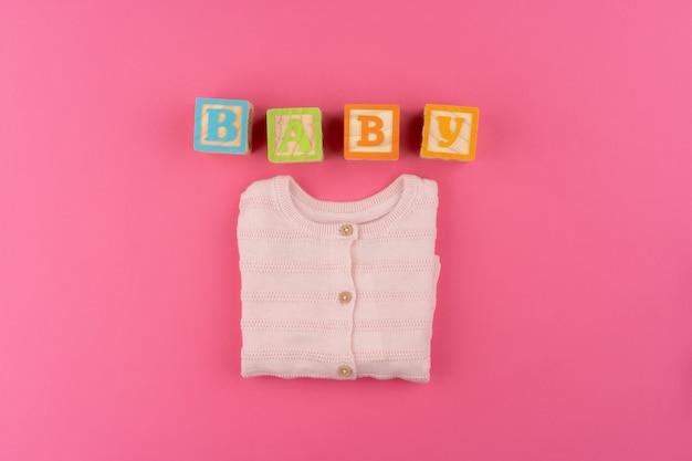 Детская одежда на розовом фоне вид сверху