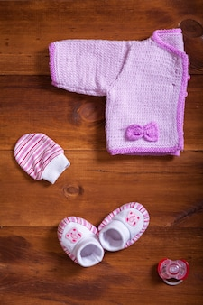 Baby clothes pink knitted sweater mittens socks and dummy on wooden table