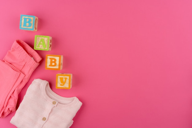 Baby clothes on pink wall top view