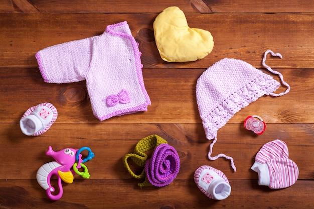 ベビー服は、茶色の木製の背景、女の子、モダンなベビーシャワーのギフト、幼児服屋、トップビューフラットレイアウトの子新生児ファッション布にコンセプト、ピンクのニット服、おもちゃ、アクセサリーを設定