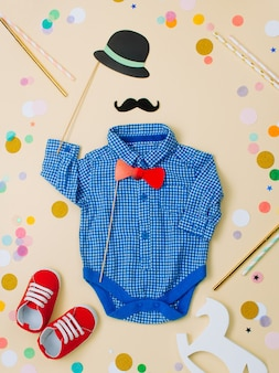 Baby clothes and shoes with paper hat, mustache and the bow tie