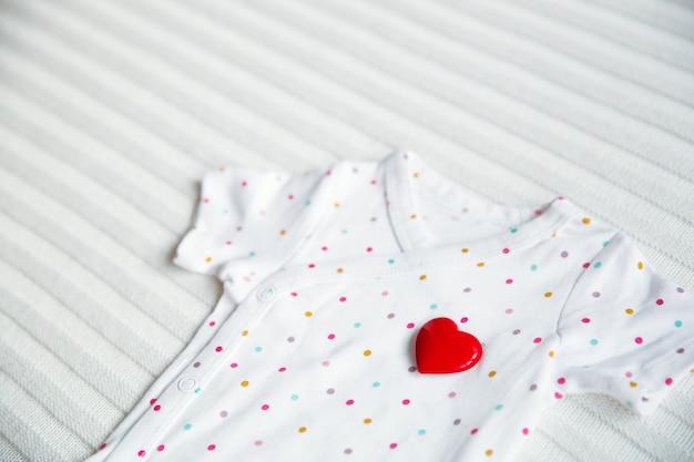 Детская одежда символ сердца на фоне белой ткани.