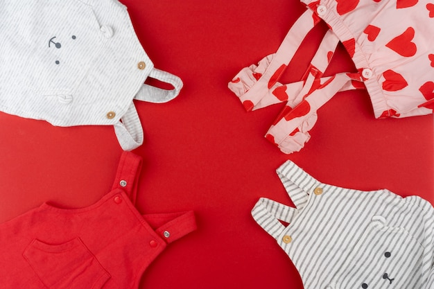 Baby clothes top view on red
