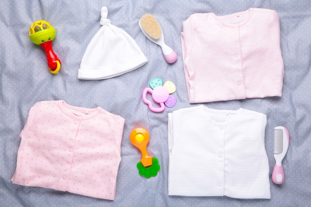 Baby clothes with a shower accessories on a grey background
