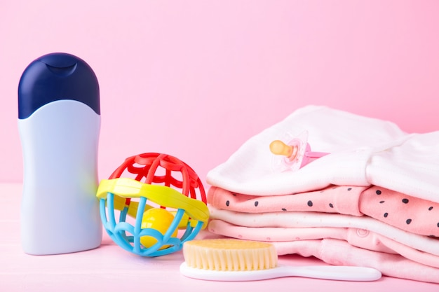 Baby clothes with a shower accessories on a pink background