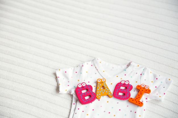 Детская одежда с игрушечными буквами baby на фоне белой ткани.