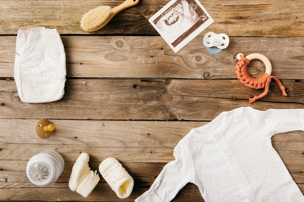 Baby clothing; milk bottle; pacifier; brush; diaper and sonography picture on wooden table