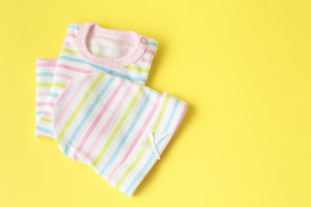 Детская одежда на желтой поверхности