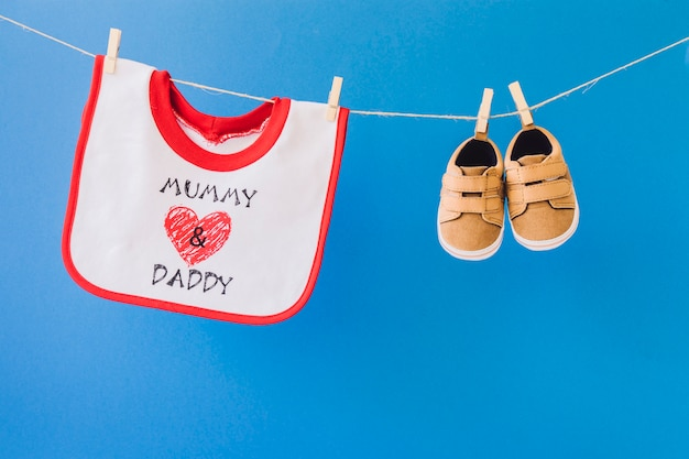 Baby concept with bib and shoes hanging on clothesline