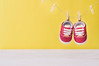 Baby concept with shoes on clothesline