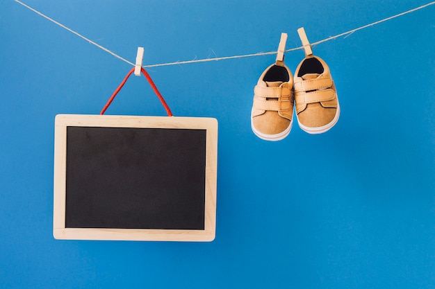 Baby concept with slate and shoes on clothesline