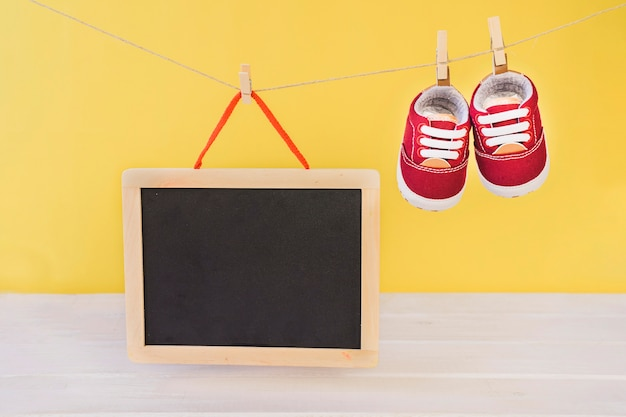 Baby concept with slate and shoes hanging on clothesline