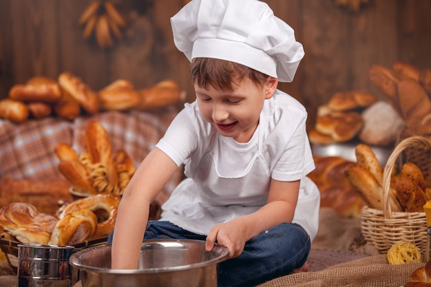 Baby cook dressed prevents whisk flour baker lots of buns. lots of bread baking. rustic style