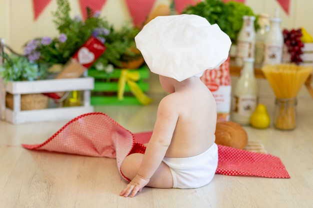 A baby in a cook's hat sits back in a beautiful photo zone with flour and vegetables, a cook's child, a child with flour and bread prepares food