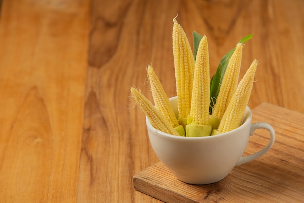 Baby corn is placed in a glass on a wooden floor.