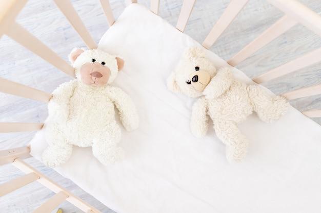 테디베어 장난감이 있는 유아용 침대, 아동용 직물 및 수면용 침대의 개념