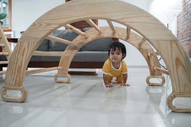 Baby crawling past under the pikler climbing toys in the house