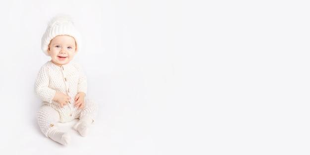아기는 흰색 격리된 배경에 따뜻한 양복과 모자를 쓰고 텍스트를 위한 공간을 크롤링합니다.