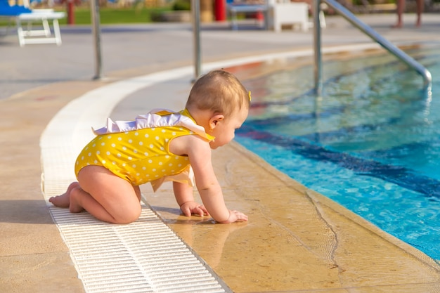 Baby crawls into the pool to the water.