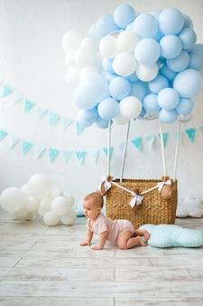赤ちゃんは、テキストの場所と風船と籐のバスケットの背景に床を這う