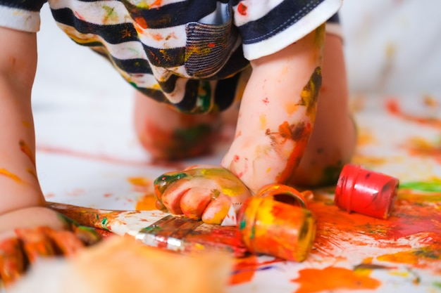 Ребенок ползает по полу, играя с красками