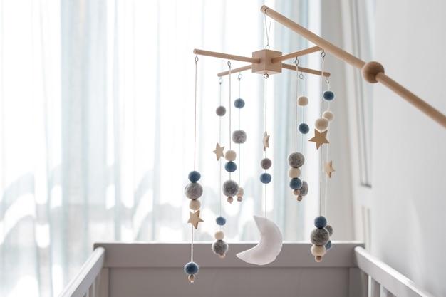 별, 행성, 달이 있는 아기 침대 이동식. 신생아 침대 위의 어린이 수제 장난감. 펠트와 나무로 만든 친환경 아기장난감을 라이트룸에 걸어두었습니다. 텍스트를 위한 공간입니다.