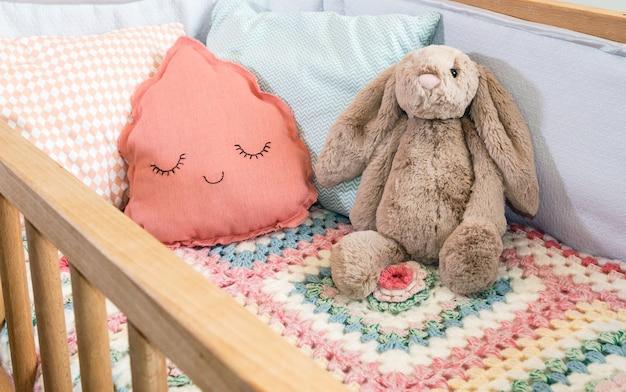 子供とおもちゃのためのクッション付きのベビーベッド。