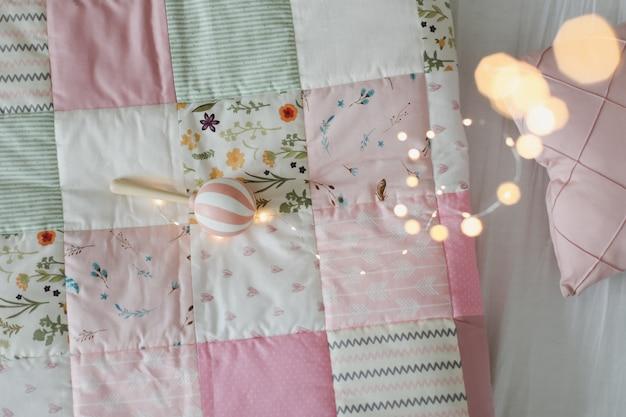 Детская кроватка с розовым пледом в стиле пэчворк и текстилем для детской комнаты