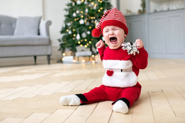Baby in cristmas costume crying on floor