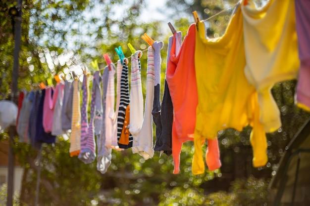 屋外の物干しにぶら下がっている赤ちゃんのかわいい服。緑の背景の庭のラインにぶら下がっている子洗濯物。ベビーアクセサリー。