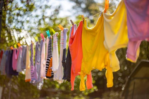 物干しにぶら下がっている赤ちゃんのかわいい服屋外の子供の洗濯物が庭のラインにぶら下がっている