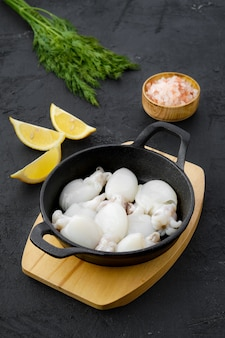 주철 프라이팬에 딜, 소금, 레몬을 넣은 아기 오징어