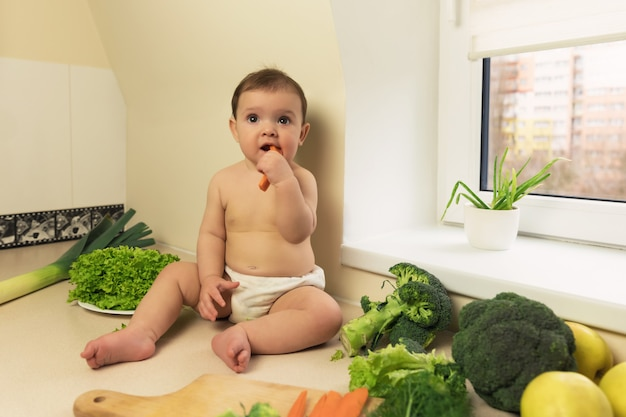 Baby in the diaper is sitting on the kitchen table and eat vegetables