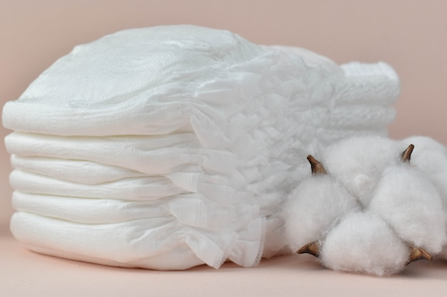 Baby diapers and dried cotton on a beige closeup.