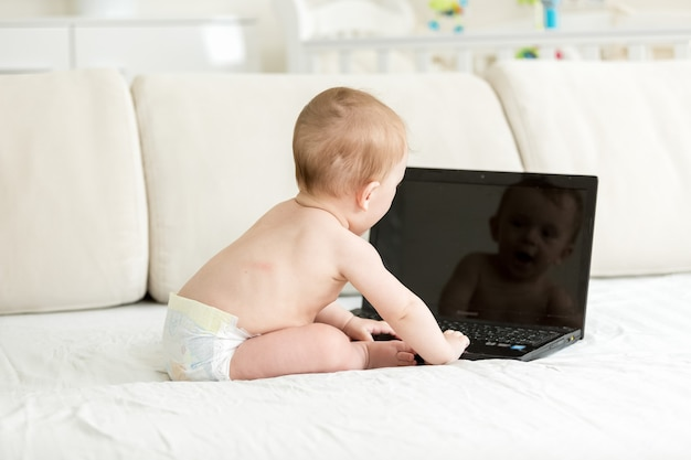 Baby in diapers sitting on bed with laptop