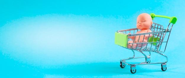 Кукла в корзине на синем фоне с местом для текста. купите ребенку.