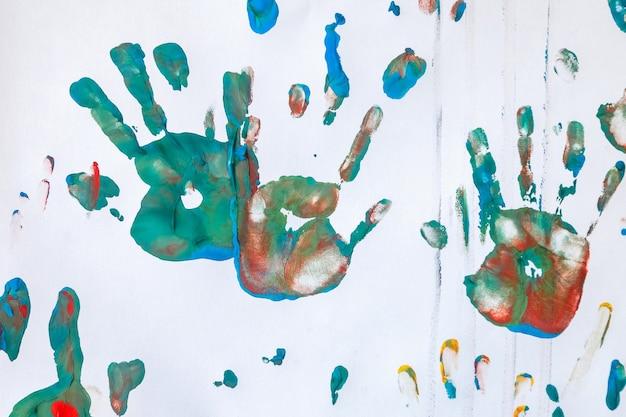 Детский рисунок с акварелью на фоне белой стены. произведения детского абстрактного эскиза. цветные детские отпечатки ладоней и грязные пятна на фотографиях. уникальные фоны для творчества и обои