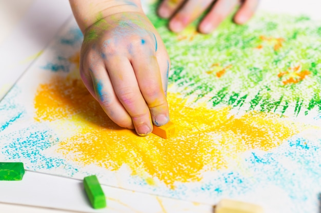 Малыш рисует карандашами.