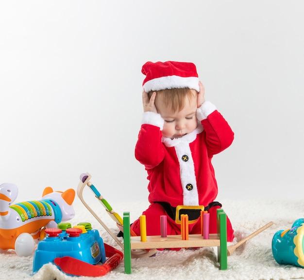 Ребенок в костюме санта-клауса сидит на полу и играет с деревянными и пластиковыми игрушками.