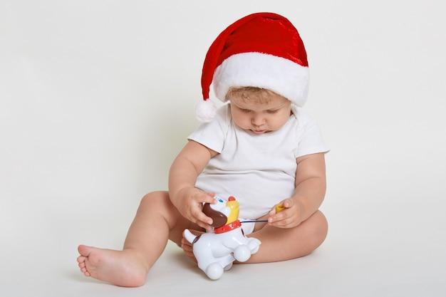 赤ちゃんは、床に裸足で座ってプラスチックの犬と遊んでいる間、白い壁の上に孤立してポーズをとっているサンタクロースの帽子を着せ、子供は興味を持っておもちゃを見ています。