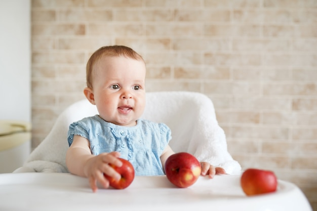 Baby eating fruit. little girl biting yellow apple sitting in white high chair in sunny kitchen