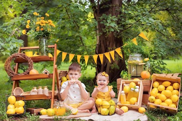 Ребенок ест лимоны и пьет лимонад на открытом воздухе летом
