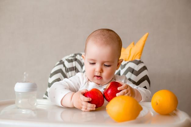 椅子に座ってマッシュフルーツを食べる赤ちゃんをクローズアップ。カメラ目線。健康的な生活様式。子供時代。