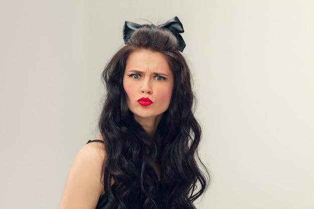 Детское лицо сердито. портрет красивой молодой женщины в серой студии