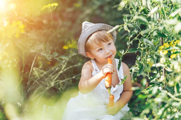 Baby farmer with carrots and cacual clother sitting in green grass