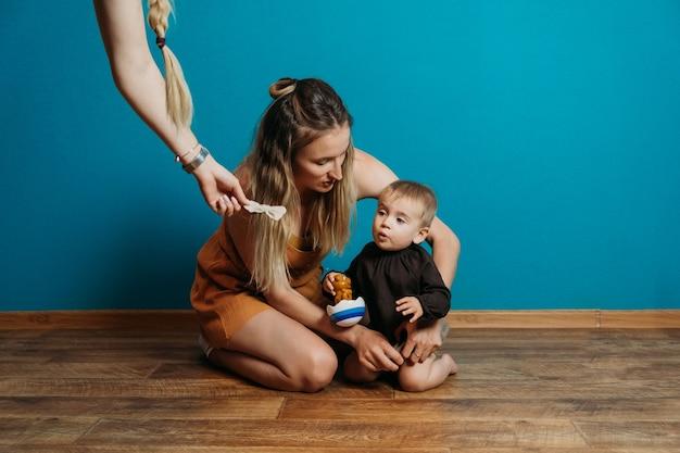 ベビーファッションはドレスとアクセサリーを選ぶお母さんは家の母親で小さな幼児の女の赤ちゃんをドレスアップします