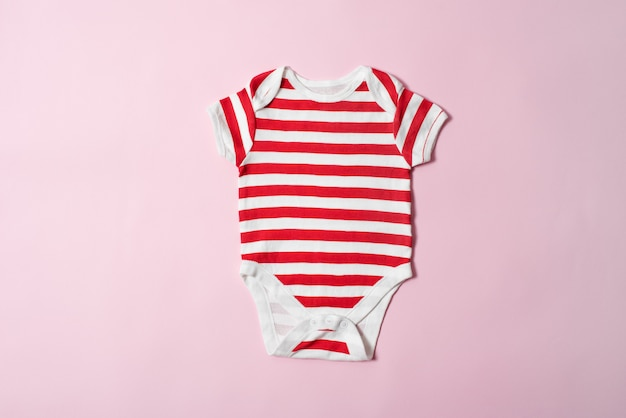 Baby fashion concept on a pink surface. striped bodysuit