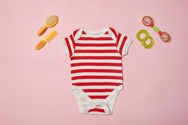 Baby fashion  on a pink . striped bodysuit, scallop and beanbag.