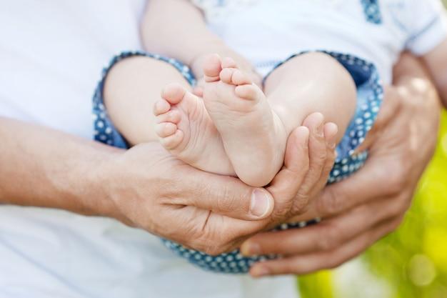 Детские ножки в руках отца. крошечные ноги ребенка на крупном плане мужских рук внешний. папа и его ребенок. концепция счастливой семьи. красивый концептуальный образ отцовства.